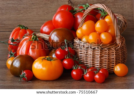Organic multicolored tomatoes  on a garden wooden table.