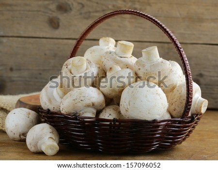 organic mushrooms (champignons) in a basket on a wooden background