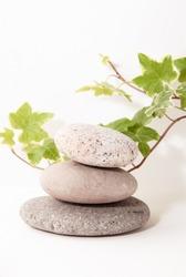 organic natural pebble stone on white background isolated closeup, stack of balanced zen stones, smooth sea pebbles pyramid, round yoga stones, yoga rocks heap, stacked balance cobblestone on table