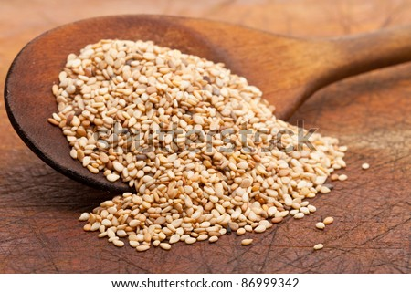 Organic natural sesame seeds on wooden spoon