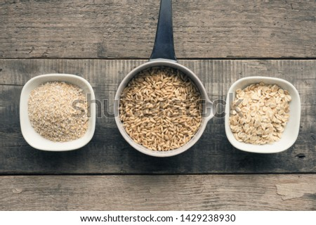 Organic oat grain, oat meal and oat bran on a rustic wooden kitchen table #1429238930