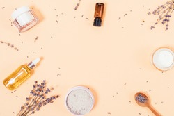 Organic oils, clay, moisturizers and lavender flowers on beige background, flat lay frame with empty place in center.