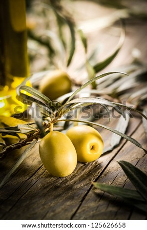 Organic olives with bottle of oil on a wooden table