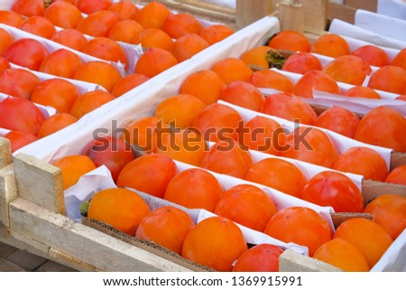 Organic, orange persimmon in wooden box are sold at local fruits farming market. Sale of fruits after harvesting. Persimmons in greengrocery. #1369915991