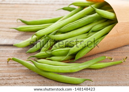 Organic pole beans in paper bag on wooden table