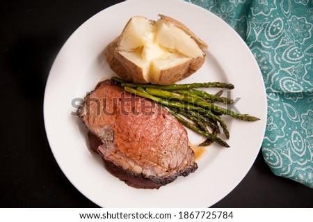 organic prime rib roast dinner with baked potato and asparagus Stockfoto ©