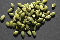 Organic pumpkin seeds in close up view on dark background.