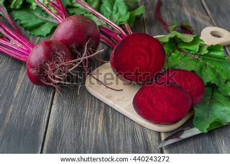 Organic red beets on an old wooden table with green leaves, rustic style