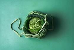 Organic savoy cabbage in a reusable shopping bag on aqua menthe table. Fabric net bag with fresh cabbage. Green monotone image with a single cabbage.