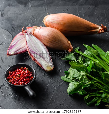 Organic shallot, bio eschalot or farm scallion raw ripe onions with greens and rose peppercorns sliced and halved black concrete textured background top view square Foto stock ©