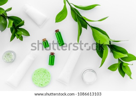 Organic skin care products. Cream, lotion, tonic. oil near green leaves on white background top view #1086613103
