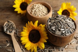 Organic sunflower seeds and flowers on wooden table