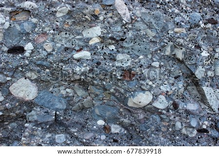 Organic texture: limestone, marble or granite gray rock consists of a gray base and includes a variety of stones of various sizes and shapes of white and brown #677839918