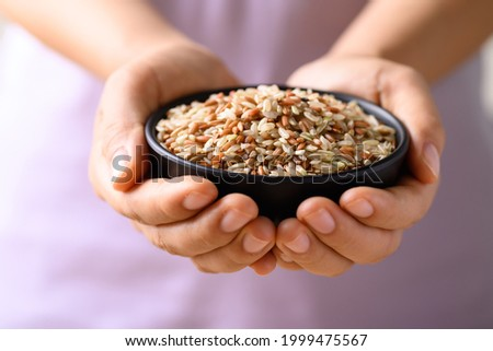 Organic Thai highland brown rice grain in a bowl holding by woman hand (Cargo rice, Loonzain rice or Husked rice), Healthy food