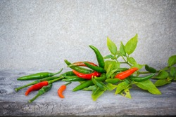 Organic Thai pepper, fresh red and green chilli on old wood background. guinea pepper ; bird pepper ; bird-chilli ; small capsicum ; chilli pepper ; tiny fiery chilli ; hot chilli