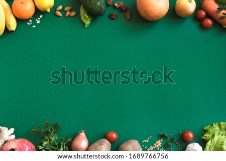Organic vegan food assortment. Healthy vegan food ingredients vegetables and fruits on green background, copy space. Clean vegan eating and detox concept.