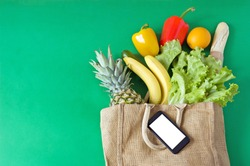 Organic Vegetables and fruits in cotton bag and phone with copy space, online market, food delivery at home concept