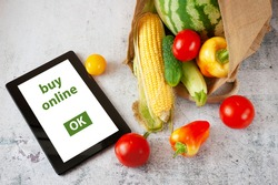 Organic Vegetables and fruits in cotton bag and tablet pc with copy space, online market, green grocery delivery at home concept