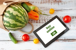 Organic Vegetables and fruits in cotton bag and tablet pc with copy space, online market, green grocery delivery at home concept, buy online concept