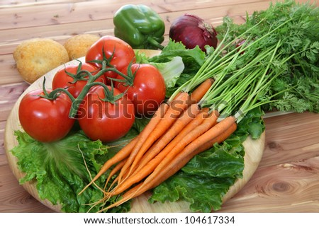 Organic vegetables in rustic setting including tomatoes on the vine, peppers, carrots, lettuce and dinner rolls