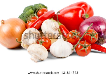Organic vegetables like onion, mushrooms, broccoli, tomatoes on vine, red pepper and red chili pepper, on white background