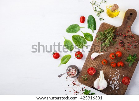 Organic vegetarian ingredients, olive oil and seasoning on rustic wooden cutting board over dark vintage background with space for text.Healthy food, or diet nutrition concept.selective focus.