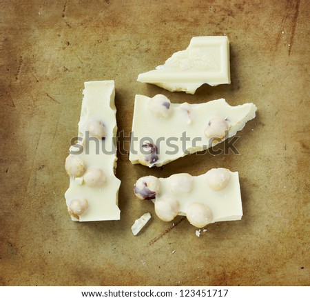 Organic, white hazelnuts chocolate on an old rustic stone chopping board - stock photo