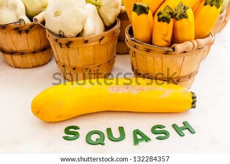 Organic yellow zucchini squash in brown bushel baskets on display at farmers market