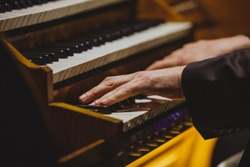 Organist's hands playing the organ
