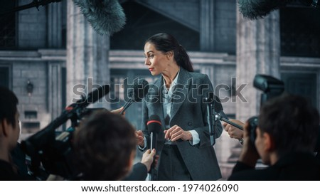 Organization Representative Answering Press Questions and Giving Interview Outside a Parliament, Court or Other Government Building. Press Officer or Businesswoman Crowded by News Journalists. Сток-фото ©