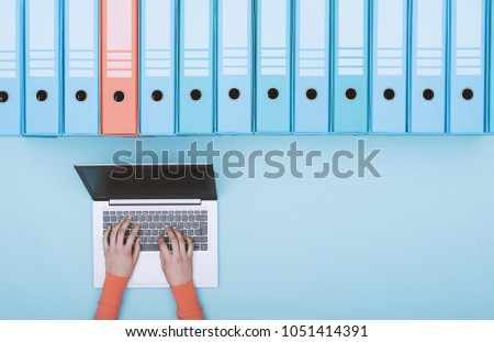 Organized archive with ring binders and woman searching for files in the database using a laptop, top view