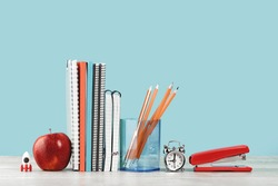 Organized office and school orange and pastel blue stationery, notebooks pencils scissors and alarm clock with red apple on grey wooden desk. Copy space for back to school education and craft concept