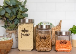 Organized pantry staples in labeled glass jars in a light and bright kitchen