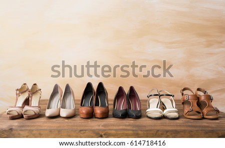 Organized woman's shoes on wooden floor #614718416