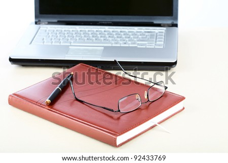 Organizer, glasses,pen and notebook on a desk