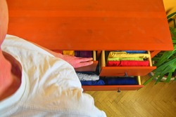Organizing and cleaning home. Man preparing orderly folded T-shirts in drawer. Man choosing orderly folded T-Shirts in drawer. Man tiding the clothes. Preparing the clothes. The order in chest of