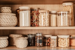 Organizing zero waste storage in kitchen. Pasta and cereals in reusable glass containers in kitchen shelf