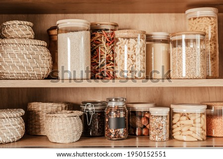 Organizing zero waste storage in kitchen. Pasta and cereals in reusable glass containers in kitchen shelf Stock photo ©