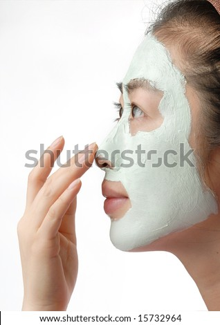 orient woman with cleansing mud mask on the face - stock photo