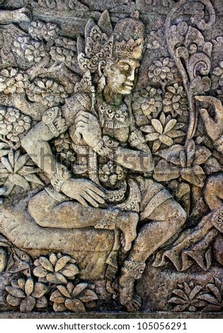 Oriental background. Woman surrounded by floral ornament. From a balinese temple - stock photo