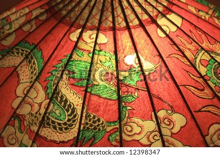 Oriental bamboo & paper umbrella with dragon painting, close-up: Dragon - the symbol of POWER for Chinese & Japanese