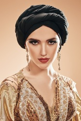 Oriental beauty woman. Portrait of a beautiful arabian woman in golsen top with traditional oriental make-up and black turban. Make-up and cosmetics.