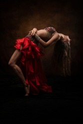 Oriental dance. Belly dance. A young girl in an oriental costume. Red. Brunette