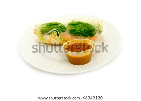 oriental  dim sum entree of spring roll shrimp vegetable in wrapper and sweet sour dipping sauce  . light plate and white background
