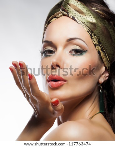 Oriental fashion style. Beautiful lady magic face. Glamor. Blowing a kiss