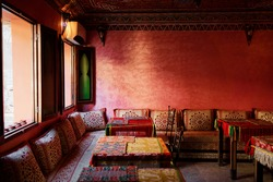 Oriental hospitality. Traveling by Morocco. Relaxing in festive moroccan traditional riad interior in medina. Comfortable terrace filled with soft, cozy furniture.