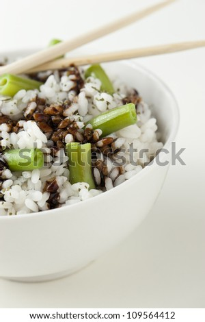 Oriental rice with green beans in a white bowl. Ready to eat