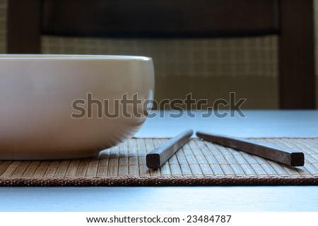 Oriental setting. Close-up white empty dish and chopsticks on bamboo mat. Front view.