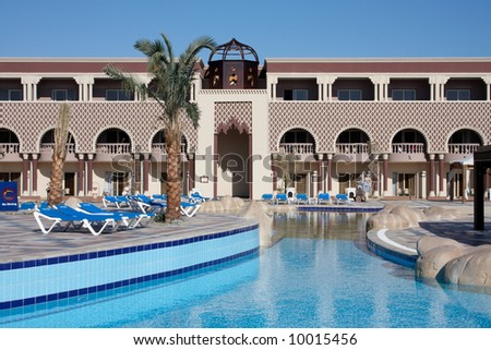 oriental style hotel with palm tree and swiming pool