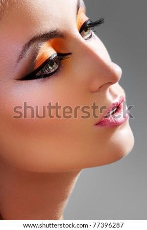Oriental style. Sensual arabic woman model. Beautiful sunburnt clean skin, saturated makeup. Bright eye make-up and dark eyeliner